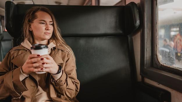 Vrouw zit in de trein en houdt een kopje koffie