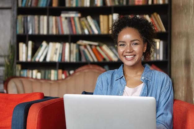 Vrouw zit in een bibliotheek met haar laptop