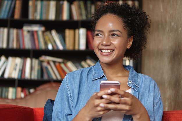 Vrouw zit in een bibliotheek met haar telefoon