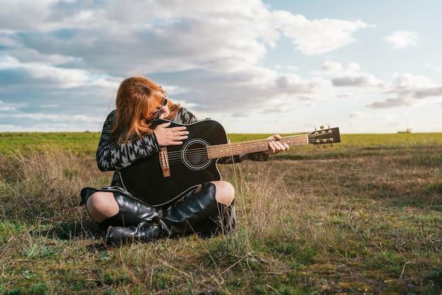 Vrouw zit in een groen veld en kijkt naar een zwarte gitaar onder een hemel met wolken