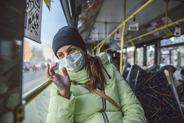 Vrouw zit in een stadsbus in een medisch beschermend masker. bescherming tegen coronavirus covid-19 in het openbaar vervoer.