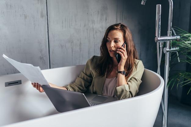Vrouw zit in het bad met papieren, laptop en praten over de telefoon.