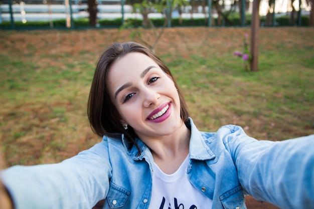 Vrouw zit in het park en maakt selfie, gelukkig