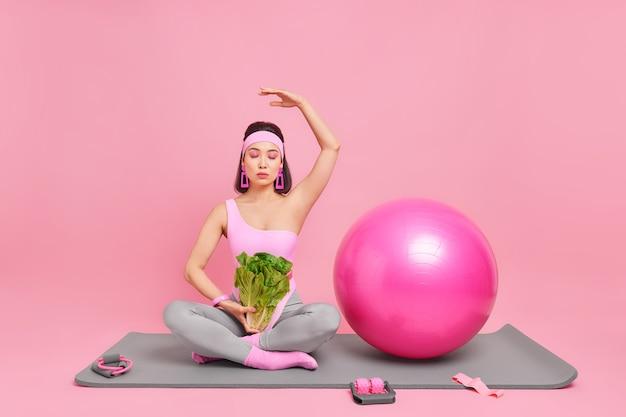 Vrouw zit in lotushouding oefen yoga houdt arm omhoog sluit ogen geniet van kalmte vredige sfeer draagt comfortabele sportuitrusting houdt groene sla salade poseert op fitnessmat binnen
