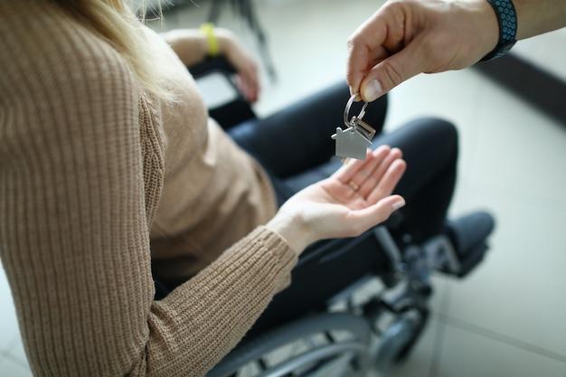 Vrouw zit in rolstoel en de sleutels worden aan haar overhandigd. huisvesting voor gehandicapten concept krijgen