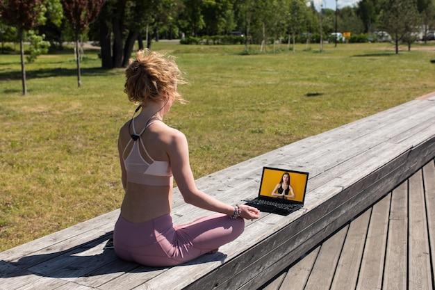 Vrouw zit in yoga pose buiten op de houten promenade en kijkt naar fitnessvideo's op laptop