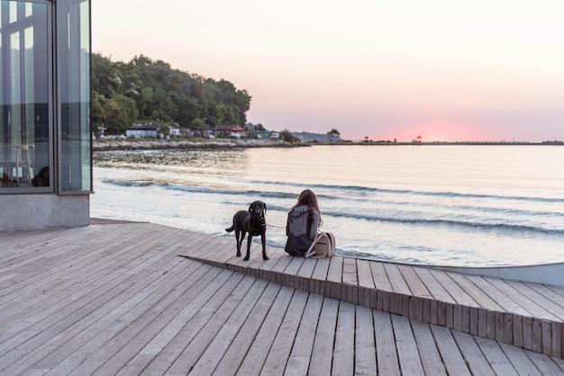 Vrouw zit met haar hond op het strand