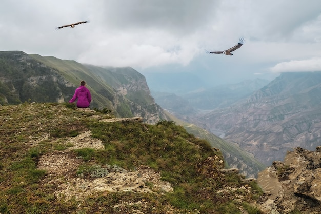 Vrouw zit met haar rug naar de bergen boven een klif, adelaars vliegen in de dramatische lucht. eenzaamheid in de bergen, solo reisconcept.