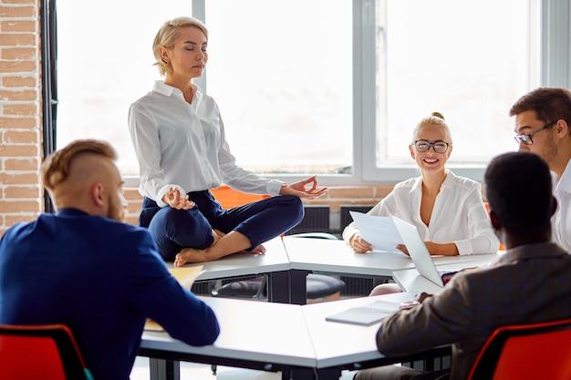 Vrouw zit ontspannen terwijl anderen brainstormen op het werk