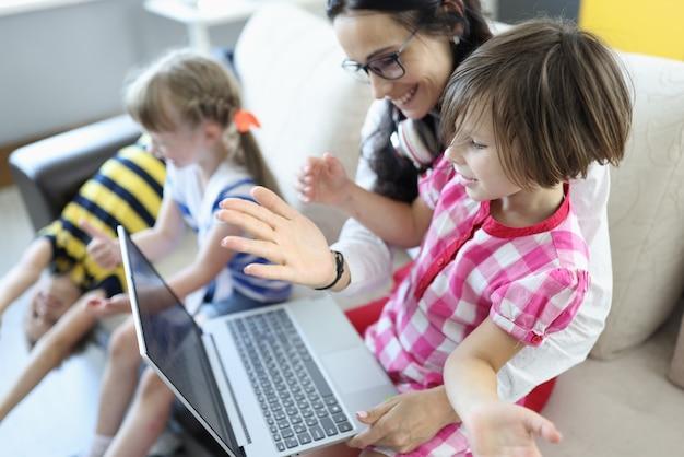 Vrouw zit op de bank, meisje zit op haar schoot, ze kijken naar laptop naast kinderen spelen.