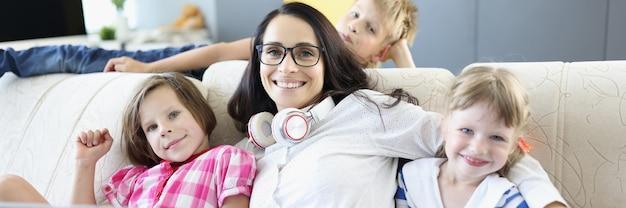 Vrouw zit op de bank met twee meisjes en een jongen staat naast laptop