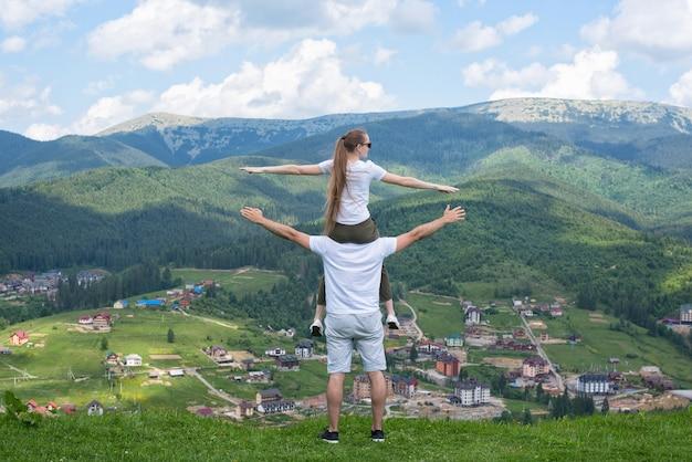 Vrouw zit op de schouders van de man en bewonder de bergen. achteraanzicht