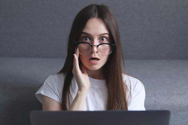 Vrouw zit op de vloer en werkt met een laptop met verbaasde uitdrukking