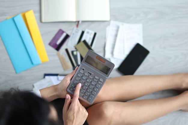 Vrouw zit op de vloer met rekenmachine naast bankpassen en rekeningen. budgetplanning en distributieconcept