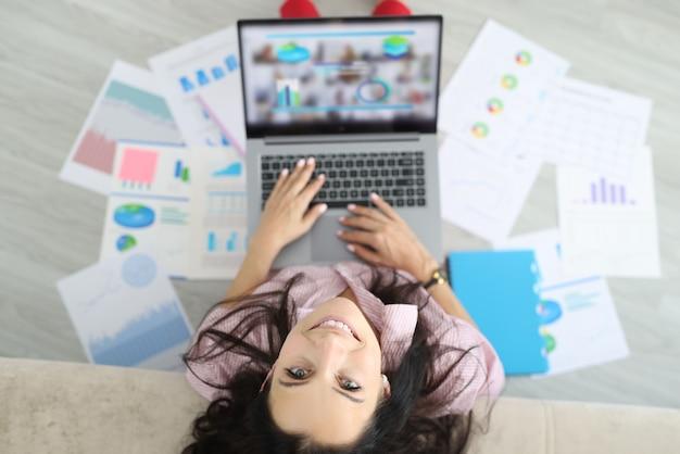 Vrouw zit op de vloer rond documenten met grafieken van commerciële indicatoren en houdt laptop vast.