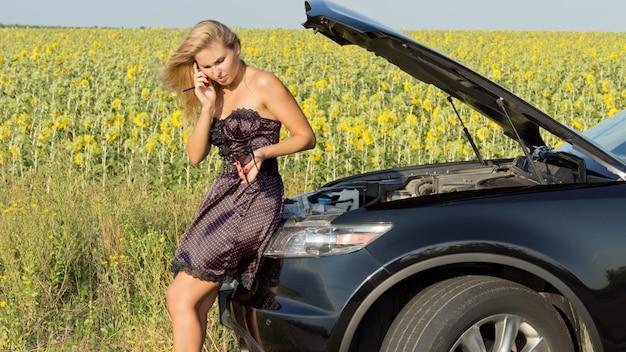 Vrouw zit op de voorkant van haar kapotte auto en belt om hulp terwijl ze op haar horloge naar de tijd kijkt