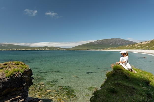 Vrouw zit op een klif en kijkt naar het kielstrand in achill island ireland