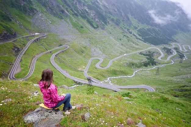 Vrouw zit op een steen genieten van prachtige berglandschap. transfagarashan highway