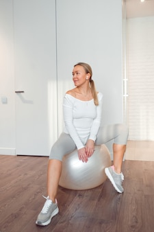 Vrouw zit op fitness bal thuis pilates oefening