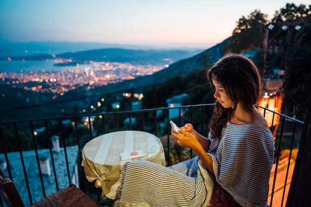 Vrouw zit op het balkon, op de achtergrond de nachtstad