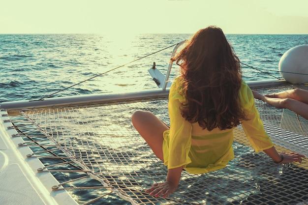 Vrouw zit op het dek van een zeilcatamaran bij zonsondergang in de zon.