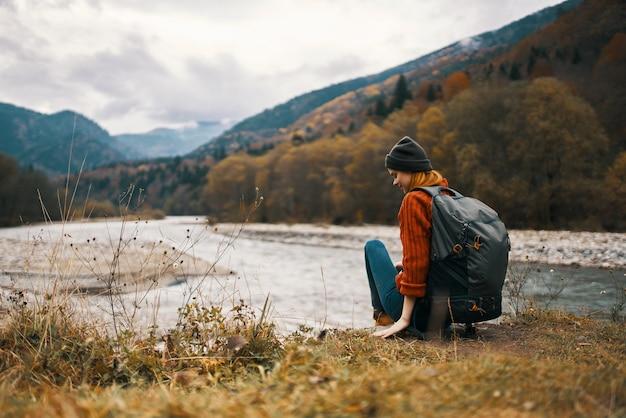 Vrouw zit op het gras in de bergen in de buurt van de rivier en de herfstlandschap