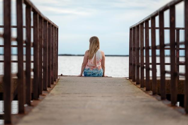 Vrouw zit op het platform en kijkt naar de zee. uitzicht vanaf de achterkant.