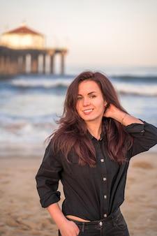 Vrouw zit op het zand voor een pier op manhattan beach in los angeles in de vroege ochtend
