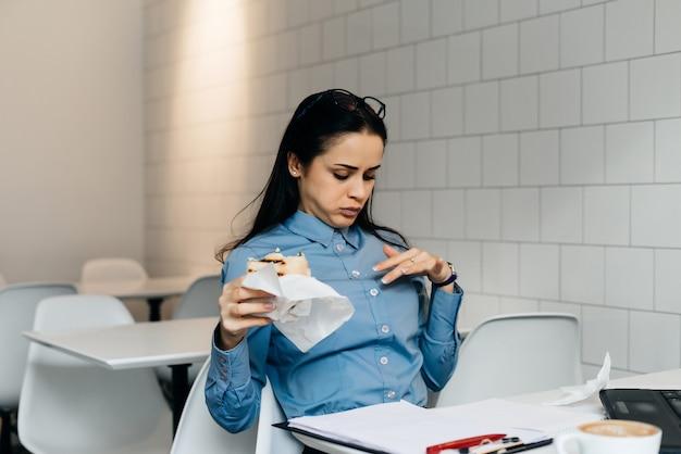 Vrouw zit op kantoor aan tafel en eet een broodje