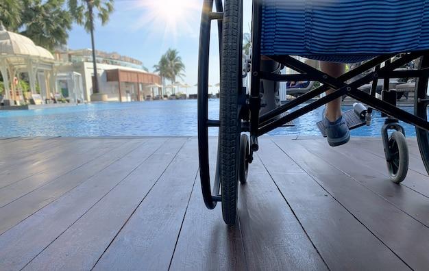 Vrouw zit op rolstoel naast zwembad