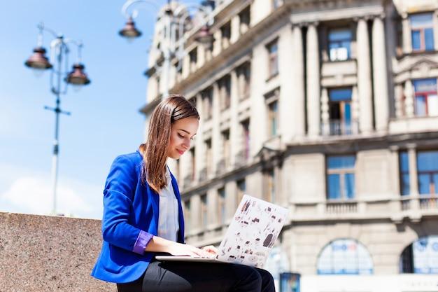 Vrouw zit op straat en werkt met een laptop