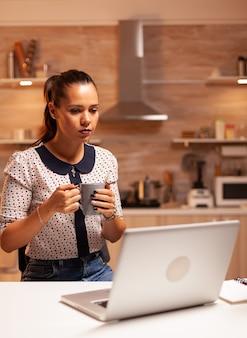 Vrouw zit 's avonds laat in de keuken en werkt aan een project voor werk met een laptop en een kopje koffie. werknemer die om middernacht moderne technologie gebruikt en overuren maakt voor werk, zaken, drukte, carrière.