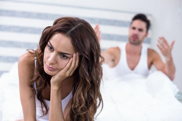 Vrouw zit terwijl man tegen haar schreeuwt
