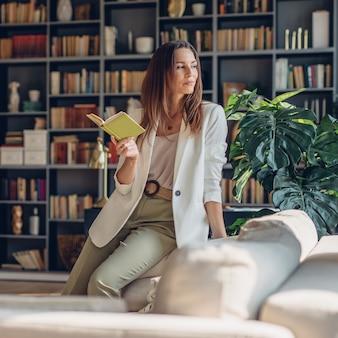 Vrouw zit thuis met open boek en kijkt bedachtzaam weg.