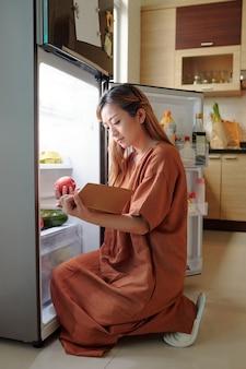 Vrouw zit voor geopende koelkast en kijkt of ze alle ingrediënten heeft voor het gerecht dat ze gaat koken