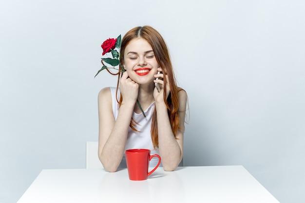 Vrouw zitten aan de tafel drinken uit een rode mok en praten over de telefoon