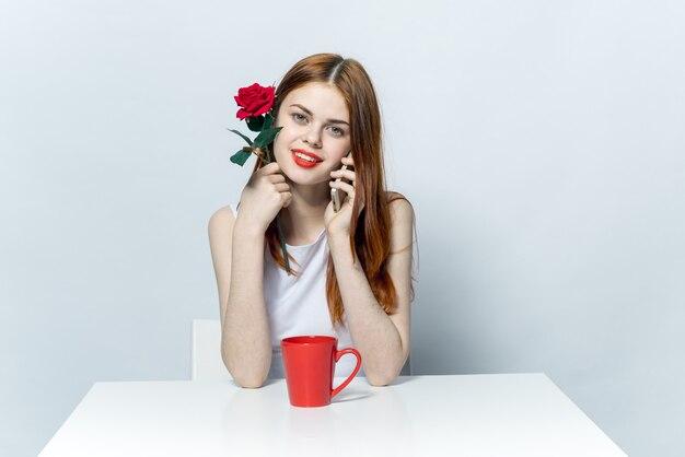 Vrouw zitten aan de tafel drinken uit een rode mok en praten over de telefoon.
