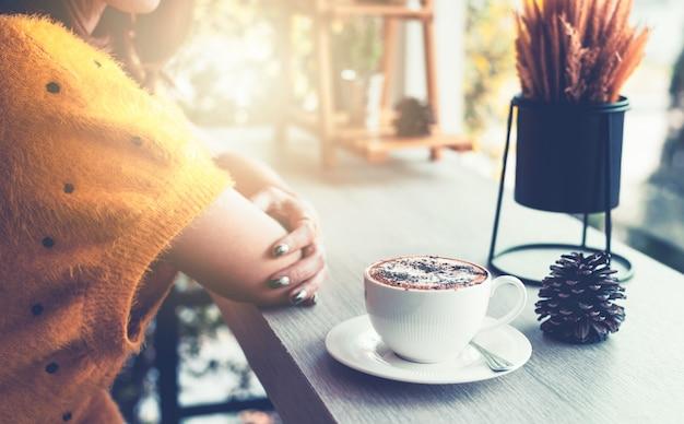 Vrouw zitten aan een tafel met een kopje koffie