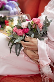 Vrouw zitten en houden bruiloft bloemen in de kamer in lange roze jurk en rode hakken.