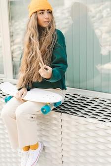 Vrouw zitten en houden skateboard