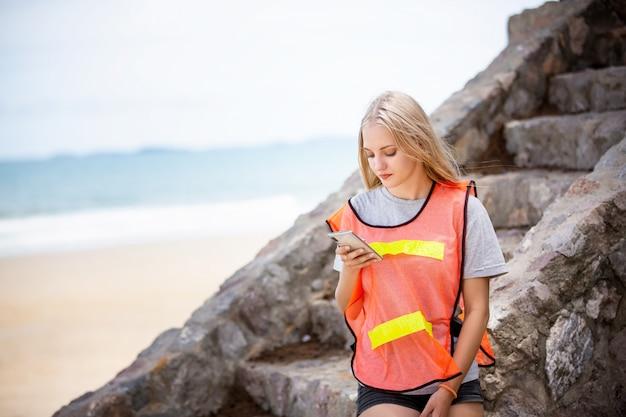 Vrouw zitten en kijken naar mobiele telefoon op het strand het dragen van een reflecterend jack van vrijwilliger.