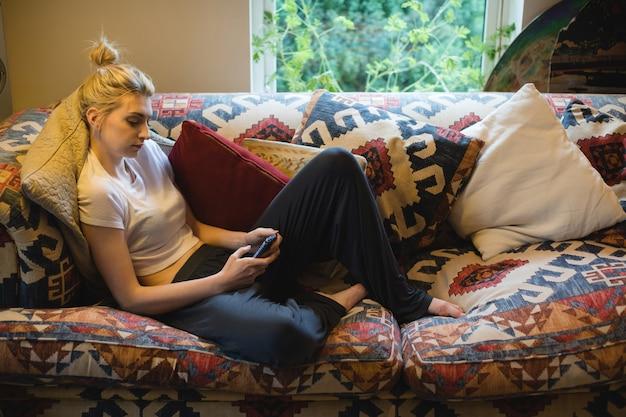 Vrouw zitten en met behulp van mobiele telefoon op de bank in de woonkamer