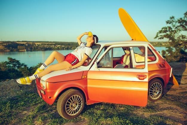 Vrouw zitten en rusten op auto op het strand op een zomerdag in de buurt van de rivier.