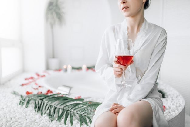 Vrouw zitten in bad versierd met rozenblaadjes