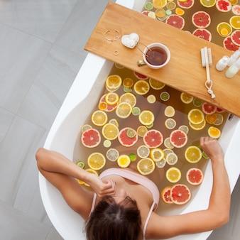 Vrouw zitten in badkuip met verse plakjes fruit