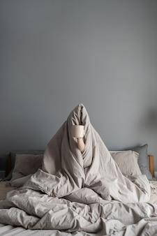 Vrouw zitten in bed, mok met koffie in de hand te houden