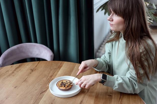 Vrouw zitten in café en cake eten