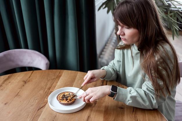 Vrouw zitten in café eten taart