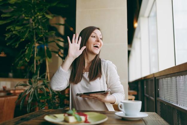 Vrouw zitten in coffeeshop aan tafel met kopje cappuccino, cake, ontspannen in restaurant tijdens vrije tijd. vrouw werkt op pc-tabletcomputer in café, zwaait, groet met de hand als iemand iemand opmerkt