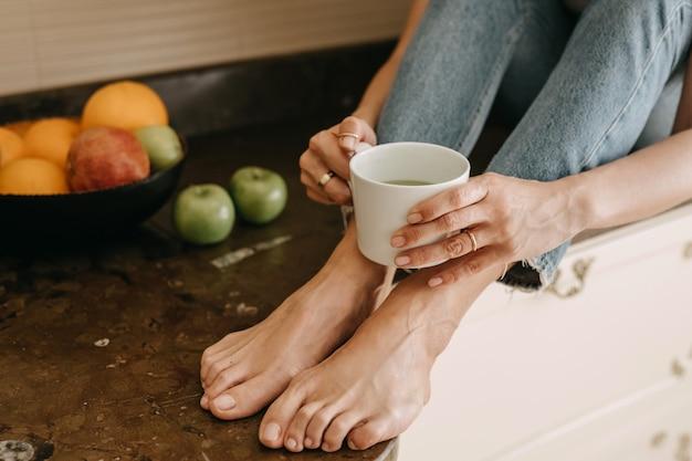 Vrouw zitten in de keuken met een kopje matcha latte